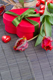 Red gift box, tulips and sweets Stock Photo