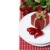 Red gift box and two hearts on a plate, roses in the background Royalty Free Stock Photo