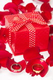 Red gift box with wedding ring and red rose petals Royalty Free Stock Images