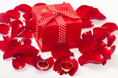 Red gift box with wedding ring and red rose petals Stock Photos