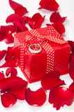 Red gift box with wedding ring and red rose petals Stock Image