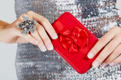 Red gift box in woman's hands. Red gift box with satin bow in hands of a young woman wearing a large flower ring and a silver sequin dress stock photography