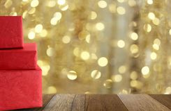 Red gift box on wooden floor and have gold bokeh background. Stock Images
