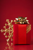 Red gift box and xmas snowflake on red background. Royalty Free Stock Photo