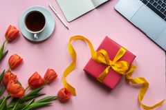Red gift box with yellow ribbon on pink background. Background with coffee, laptop and flowers. stock image