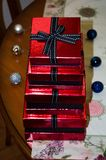 Red gift boxes with black ribbon. And shining balls on handmade tablecloth Stock Photo