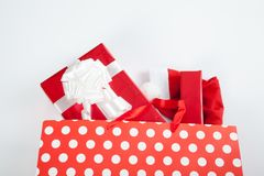 Red gift boxes and and christmas hat in shopping bags Stock Photos