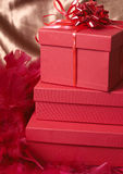 Red gift boxes with feathers and a bow. On golden silk background Royalty Free Stock Photography