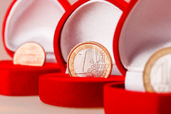 Red gift boxes with one euro, ten roubles and one cent coins. Royalty Free Stock Photo
