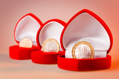 Red gift boxes with one euro, ten roubles and one cent coins. Stock Images