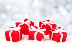 Red gift boxes in snow with twinkling lights Royalty Free Stock Image