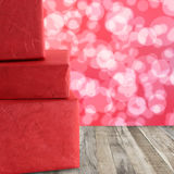 Red gift boxes stacked on a wooden floor and red bokeh abstract Royalty Free Stock Photos