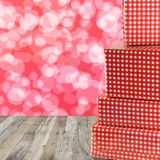 Red gift boxes stacked on a wooden floor and red bokeh abstract Stock Photo