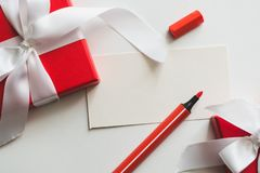 Red gift boxes tied with a white ribbon, a marker and card with copy space on a light background stock photo