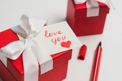 Red gift boxes tied with a white ribbon, a marker and a card with an inscription `love you` on a light background. The process of preparing a gift for a loved