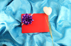 Red gift card with ribbon. On blue satin Stock Images