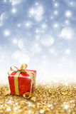 Red gift on golden glitter Stock Images