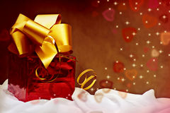 Red gift with golden ribbon with hearts. Stock Image