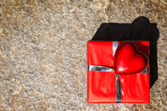 Red gift and heart on stony background Royalty Free Stock Photo