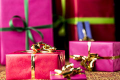 Red Gift Parcel amidst other Presents. Six gift boxes wrapped in magenta, crimson and blue. Focus is on the golden bow around the small crimson box in the front Stock Images