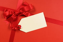 Red gift ribbon bow background with blank tag or manila label, copy space. Red gift ribbon and bow with blank tag or label Royalty Free Stock Photo
