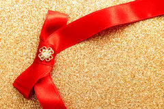 Red gift ribbon bow. On gold shiny background Stock Images