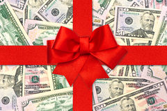 Red gift ribbon bow over american dollars Royalty Free Stock Photo