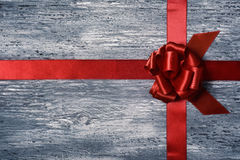 Red gift ribbon bow on a wooden surface Royalty Free Stock Photos
