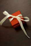 Red gift with a satin ribbon. On a wooden background Royalty Free Stock Image