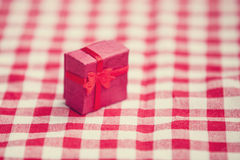 Red gift on tablecloth. Royalty Free Stock Image