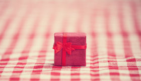 Red gift on tablecloth. Royalty Free Stock Images