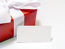 Red Gift with Tag. Gift box wrapped in red paper, tied with a white ribbon, with a blank white card for wording to be added for Christmas or Valentines Day Stock Photos