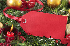 Red gift tag hanging on a christmas tree with decorations, copy space royalty free stock photo