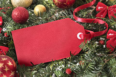Red gift tag hanging on a christmas tree with decorations, copy space royalty free stock images