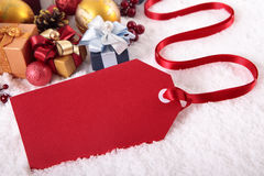 Red gift tag with various gifts and Christmas decorations on white snow background Royalty Free Stock Photography