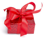 Red gift tied up by a bow. On the white isolated background Stock Photos