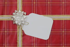 Red gift wrapped package with large blank tag Royalty Free Stock Photos