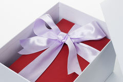 Red giftbox with bow ribbon inside open white box Royalty Free Stock Image