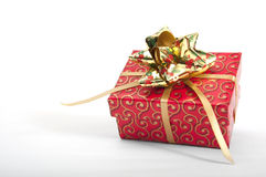 Red giftbox with golden bow. Giftbox wripped in red paper with golden bow isolated on white stock photo
