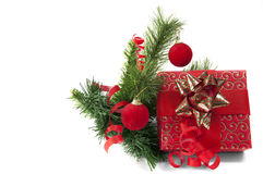 Red giftbox with new year's decoration. Giftbox wrapped in red paper with crhristmas tree an decoration on white Stock Image