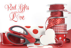 Red Gifts are filled with Love, greeting with polka dot and plain ribbons, scissors, and wrapping paper Stock Photo