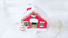 Red gingerbread house on a white snowy background. Royalty Free Stock Photography