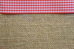 Red gingham on jute. Red ribbon on woven jute Royalty Free Stock Image