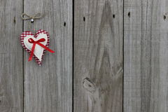 Red gingham and muslin hearts hanging on wood door. Red gingham and muslin hearts with red ribbon hanging from rope on wood door Royalty Free Stock Photography