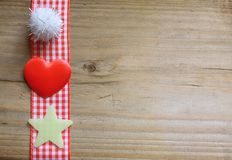 Red gingham ribbon, a fluffy ball, a star and a love heart. Red gingham ribbon a fluffy ball, a star and a love heart on a rustic wooden surface Stock Images