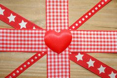 Red gingham ribbon and a love heart forming the union jack flag. Red gingham ribbon and a love heart on rustic wood forming the union jack flag Royalty Free Stock Photos