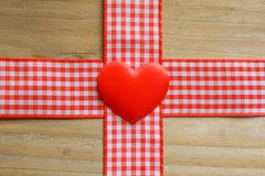 Red gingham ribbon and a love heart. On rustic wood Royalty Free Stock Images