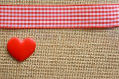 Red gingham ribbon and a love heart. On woven jute Stock Photography