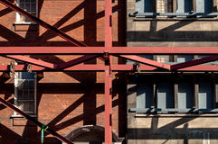Red Girders Supporting Old Building. Criss-Cross of beans and steel girders on the exterior of old building Royalty Free Stock Image