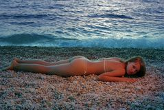 Red girl near blue sea (sunset light). Abstract red girl in bikini laying on a beach in sunset light Stock Images